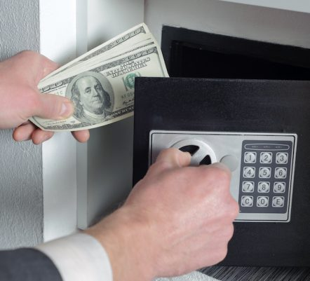 Man with one hand opens the safe  and the other holds money